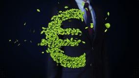 De zakenman wat betreft groen blad EURO geld, muntteken, maakte van bladeren stock footage