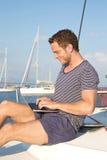 De zakenman werkt met laptop tijdens vakantie aan een zeilboot Stock Foto