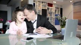 De zakenman werkt van huis en behandelt zijn kleine dochter stock video