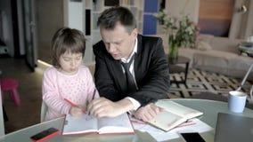 De zakenman werkt van huis en behandelt zijn kleine dochter stock videobeelden