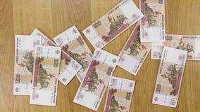 De zakenman werpt roebels op houten lijst, achtergrond van geld stock video