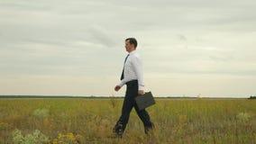 De zakenman in wit overhemd in blauwe band met zwarte aktentas loopt door het park voor een belangrijke vergadering stock footage