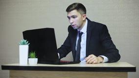 De zakenman wordt geschokt door laptop analyse, komt de rook uit computer stock footage