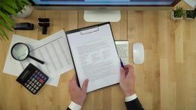 De zakenman Working On Computer en het Ondertekenen van Documentvlakte lag stock videobeelden