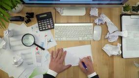 De zakenman Working At Table met Verfrommelde Documenten Vlakte lag stock footage