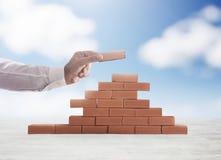 De zakenman zet een baksteen om een muur te bouwen Concept nieuw zaken, vennootschap, integratie en opstarten stock foto