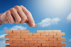 De zakenman zet een baksteen om een muur te bouwen Concept nieuw zaken, vennootschap, integratie en opstarten stock foto's