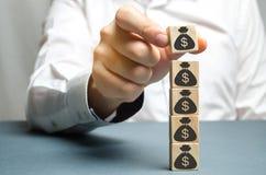 De zakenman zet een blok met een beeld van dollars Verhoogde begroting en winsten in het team De hoofdaccumulatie en stock afbeelding