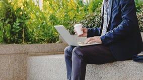 De zakenman zit en werkend aan laptop over gegevens van middelen voorzie openlucht met koffie stock afbeelding