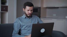 De zakenman zit op bank en werkt thuis gebruikend moderne computer voor professionele mededeling stock videobeelden