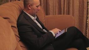 De zakenman zit op een bank en opent tablet stock video