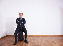 De zakenman zit op zijn bagage Stock Fotografie