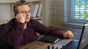 De zakenman zit voor computer, die op celtelefoon spreken en blijft ontevreden met het gesprek stock videobeelden