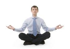 De zakenman zit in yogapositie stock afbeeldingen