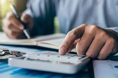 De zakenmanaccountant die nota's maken bij rapport die financi?n doen en berekent over investeringskosten en het analyseren van f royalty-vrije stock foto's
