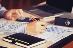 De zakenmanhand die aan grafiek rapport richten en berekent Stock Fotografie