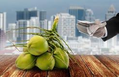 De zakenmanhand koopt kokosnotenfruit met stadsachtergrond royalty-vrije stock afbeeldingen