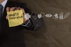 De zakenmanhand trekt ziektekostenverzekering met kleverige nota en med Stock Foto