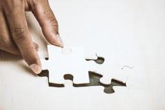 De zakenmanhand zette het laatste stuk van puzzel Royalty-vrije Stock Afbeeldingen