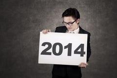 De zakenmanholding scheept het Nieuwjaar 2014 in Stock Afbeelding