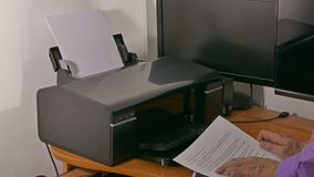De zakenmanmens in bureau drukt documenten bij printer het typen op tablet stock footage