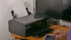 De zakenmanmens in bureau drukt documenten op printer stock videobeelden