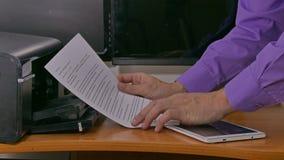 De zakenmanmens in bureaudrukken onderzoekt documenten bij printer het typen op tablet stock videobeelden
