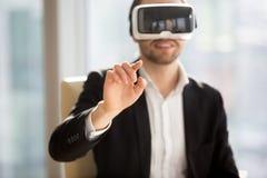 De zakenmanwerken in bureau vergrote werkelijkheid stock foto's