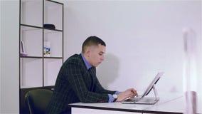 De zakenmanwerken in een bureau bij de lijst met computer stock video