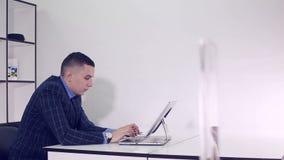 De zakenmanwerken in een bureau bij de lijst met computer stock footage