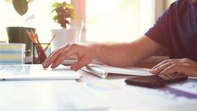 De zakenmanwerken met laptop, smartphone en het typen op het toetsenbord stock videobeelden