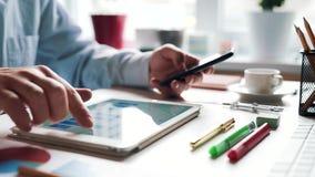 De zakenmanwerken met smartphone en tabletcomputer en studiesfinanciële informatie stock videobeelden