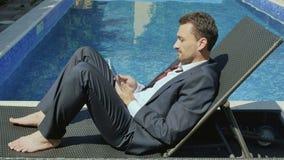 De zakenmanwerken met tablet dichtbij het zwembad stock videobeelden