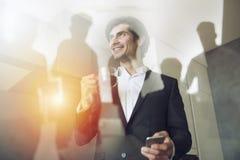 De zakenmanwerken met zijn smartphone in bureau Dubbele blootstelling royalty-vrije stock foto's