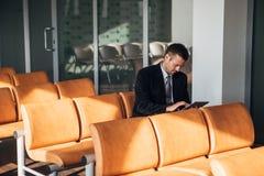 De zakenmanzitting in het bureau en gebruikt de tablet stock foto's