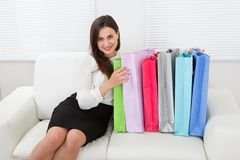 De Zakken die van onderneemsterwith multicolored shopping op Bank zitten Stock Fotografie
