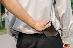 De zakkenroller die a stelen bemant portefeuille van achterzak stock afbeelding