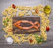 De zalm in de vorm van vissen, rond hem wordt opgemaakt spreidde de ingrediënten voor het maken van deegwaren, kruidenkruiden op  royalty-vrije stock afbeeldingen