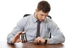 De zandloper van de zakenmanholding stock afbeeldingen