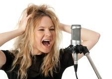 De zanger die van de rots aan de microfoon gilt stock fotografie