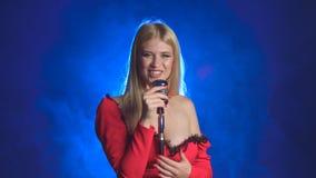 De zanger in een rode kleding zingt in een retro microfoon Rook achtergrond stock footage