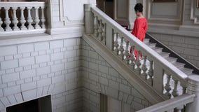 De zanger in elegante rode kleding op hoge hielen beklimt een grote trap bij mooie zaal stock video