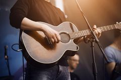 De zanger speelt een gitaar van donkere kleur stock afbeelding