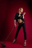 De zanger van de schoonheid in zwart leer op rood met mic Stock Afbeeldingen
