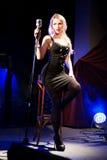 De zanger van de zangervrouw zingt een lied met retro microfoonzitting op stoel overleg Stock Afbeeldingen