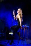 De zanger van de zangervrouw zingt een lied met retro microfoonzitting op stoel overleg Royalty-vrije Stock Foto's