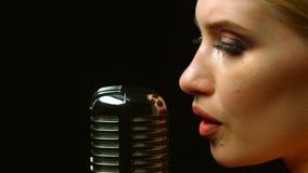 De zanger voert liederen in een retro microfoon uit Zwarte achtergrond Sluit omhoog stock footage
