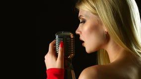 De zanger zingt in een retro microfoon Zwarte achtergrond Sluit omhoog stock footage