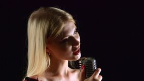 De zanger zingt in een retro microfoon Zwarte achtergrond Sluit omhoog Zachte nadruk stock video