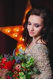 De zangervrouw schittert binnen kleding met broadway ster op achtergrond Krullend kapsel, perfecte samenstelling Bloemen in haar  Stock Fotografie